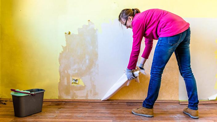 Woman repairing a wall in apartment, concept of home renovating by individual people.