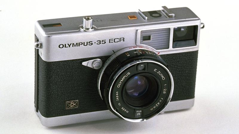 "An Olympus-35 ECR rangeinfer-style camera with a short ""pancake"" lens is seen here against a white background"