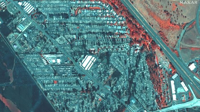 An infrared image shows destroyed homes in Phoenix, Oregon: burned vegetation and property appear grey, surviving vegetation is in red