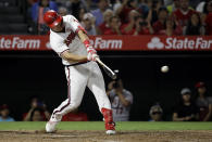 FILE - In this Aug. 17, 2019, file photo, Los Angeles Angels' Mike Trout drives in two runs with a single against the Chicago White Sox during the seventh inning of a baseball game in Anaheim, Calif. The average salary in the major leagues has dropped in consecutive years for the first time since the players' association started keeping records more than a half-century ago. This year's drop followed two slow free-agent markets and new contracts with large signing bonuses for Trout, Alex Bregman, Jacob deGrom, Paul Goldschmidt, Manny Machado and A.J. Pollock. (AP Photo/Marcio Jose Sanchez, File)