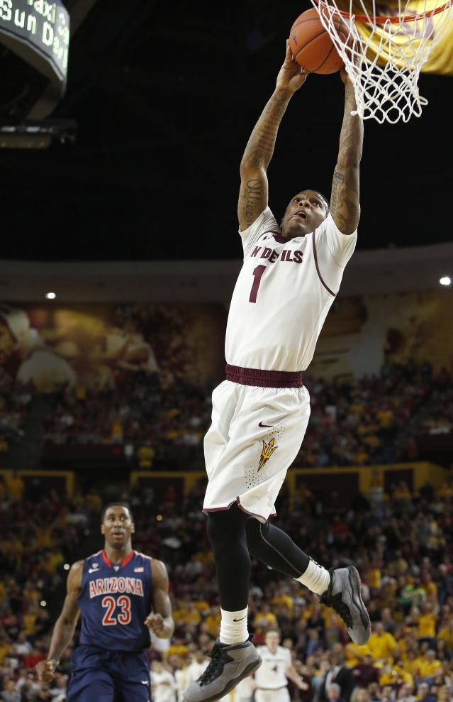 Arizona State's Jahii Carson (1) goes up to dunk as Arizona's Rondae Hollis-Jefferson (23) looks on during the first half of an NCAA college basketball game on Friday, Feb. 14, 2014, in Tempe, Ariz. (AP Photo/Ross D. Franklin)
