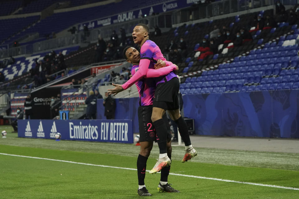 Paris Saint Germain's Kylian Mbappe, right, celebrates with Abdou Diallo after he scored a goal against Lyon during the French League One soccer match between Lyon and PSG in Decines, near Lyon, central France, Sunday, March 21, 2021. (AP Photo/Laurent Cipriani)