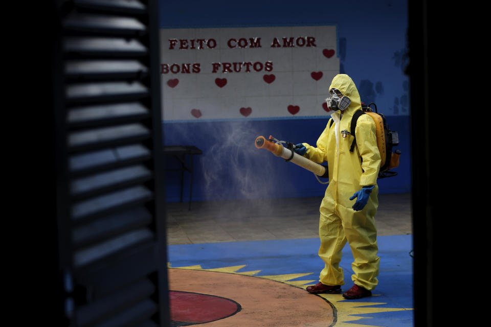 A government employee disinfects a public school as a measure against the spread of the new coronavirus, in the Taguatinga neighborhood of Brasilia, Brazil, Tuesday, July 28, 2020. The local government has began preparing for the safereopening of schools in mid-August, asrestrictionsrelated to the COVID-19 lockdownare eased. (AP Photo/Eraldo Peres)
