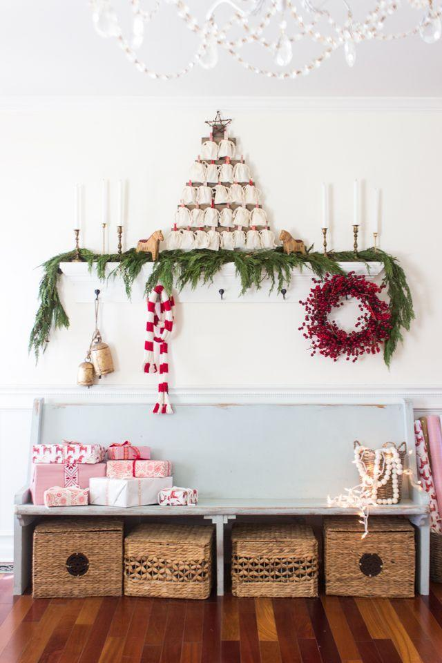 """<p>The entryway is the first thing guests see when they walk in, so make sure it's decked out in the spirit of Christmas. We love the details here, from the <a href=""""https://www.countryliving.com/diy-crafts/how-to/g1053/gift-wrapping-ideas/"""" rel=""""nofollow noopener"""" target=""""_blank"""" data-ylk=""""slk:pretty wrapped presents"""" class=""""link rapid-noclick-resp"""">pretty wrapped presents</a> to the <a href=""""https://www.countryliving.com/diy-crafts/tips/g2151/advent-calendars/"""" rel=""""nofollow noopener"""" target=""""_blank"""" data-ylk=""""slk:creative advent calendar"""" class=""""link rapid-noclick-resp"""">creative advent calendar</a>.</p><p><strong>Get the tutorial at <a href=""""http://www.shadesofblueinteriors.com/traditional-christmas-home-tour/"""" rel=""""nofollow noopener"""" target=""""_blank"""" data-ylk=""""slk:Shades of Blue Interiors"""" class=""""link rapid-noclick-resp"""">Shades of Blue Interiors</a>.</strong></p><p><a class=""""link rapid-noclick-resp"""" href=""""https://www.amazon.com/Tatuo-Pieces-Drawstring-Reusable-Storage/dp/B07G16YNPK?tag=syn-yahoo-20&ascsubtag=%5Bartid%7C10050.g.1247%5Bsrc%7Cyahoo-us"""" rel=""""nofollow noopener"""" target=""""_blank"""" data-ylk=""""slk:SHOP FAVOR BAGS"""">SHOP FAVOR BAGS</a></p>"""