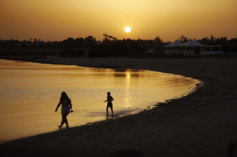 FILE - In this file photo dated Sunday, May 17, 2020, beachgoers walk in the sea water during sunset at an empty stretch of Dome beach at Makrinissos in Cyprus' seaside resort of Ayia Napa, a favorite among tourists.  Cyprus' government Wednesday May 27, 2020, is pledging to cover all costs for anyone testing positive for the coronavirus while on vacation in the east Mediterranean island nation, covering the costs of lodging, food, drink and medication for COVID-19 patients and their families.  (AP Photo/Petros Karadjias, FILE)