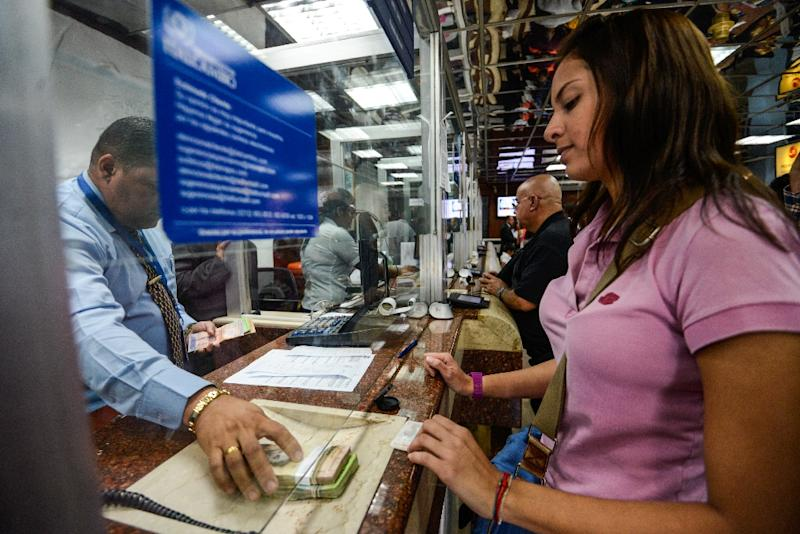 A customer receives money at a currency exchange office in Caracas on February 19, 2015