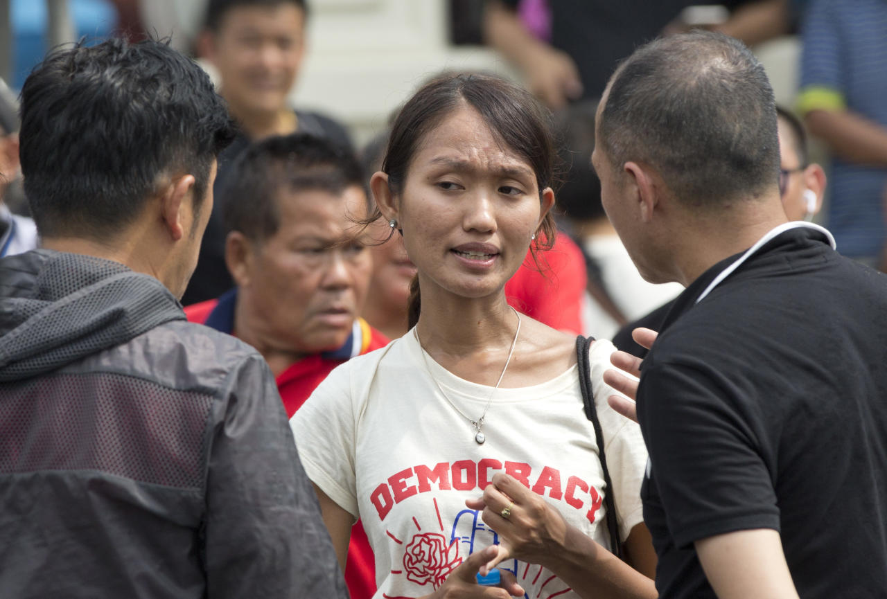 Thai pro-democracy leader Chonthicha Jangrew, center, tries to negotiate with plain clothed police officers during a protest march to mark the fourth anniversary of the military take-over of government in Bangkok, Thailand, Tuesday, May 22, 2018. Police in the Thai capital deployed about 3,200 officers to block a march by about 200 demonstrators, and arrested several leaders including Jangrew for protesting four years of military rule and calling for elections this year. (AP Photo/Gemunu Amarasinghe)