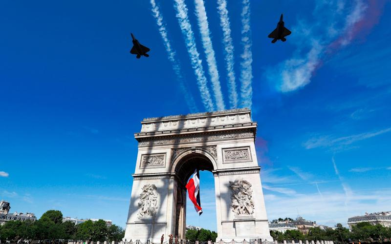 Two F22 of the US Air Force fly over the Arc de Triomphe in Paris on July 14, 2017 - AFP