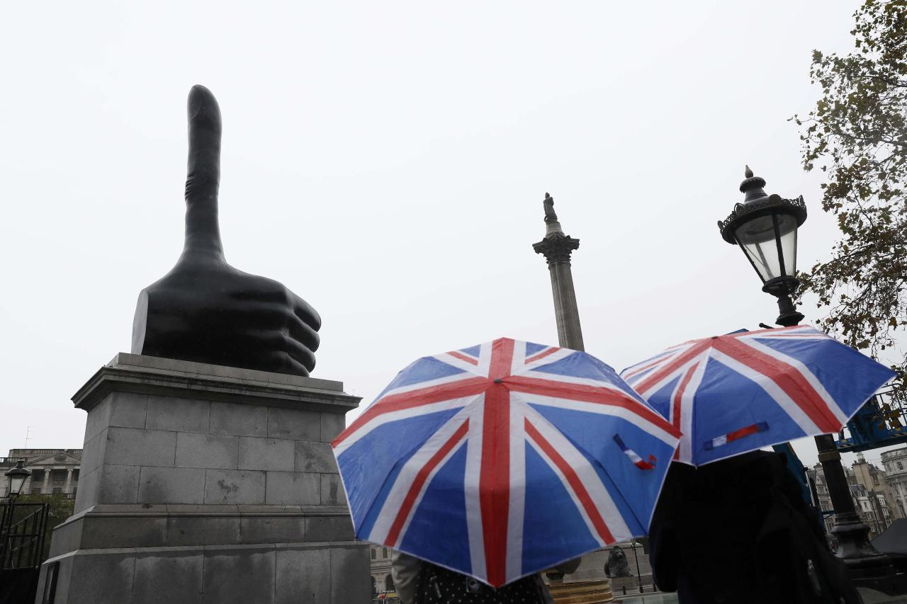"Tourists with union jack umbrellas look at the artwork ""Really Good"" by David Shrigley on the fourth plinth at Trafalgar Square in central London, Britain September 29, 2016.  REUTERS/Stefan Wermuth FOR EDITORIAL USE ONLY."
