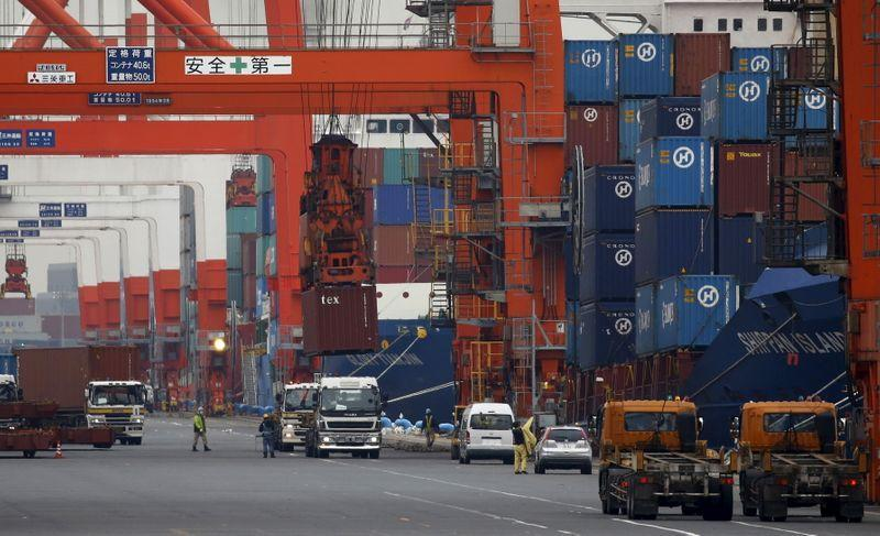 Workers load containers onto trucks from a cargo ship at a port in Tokyo