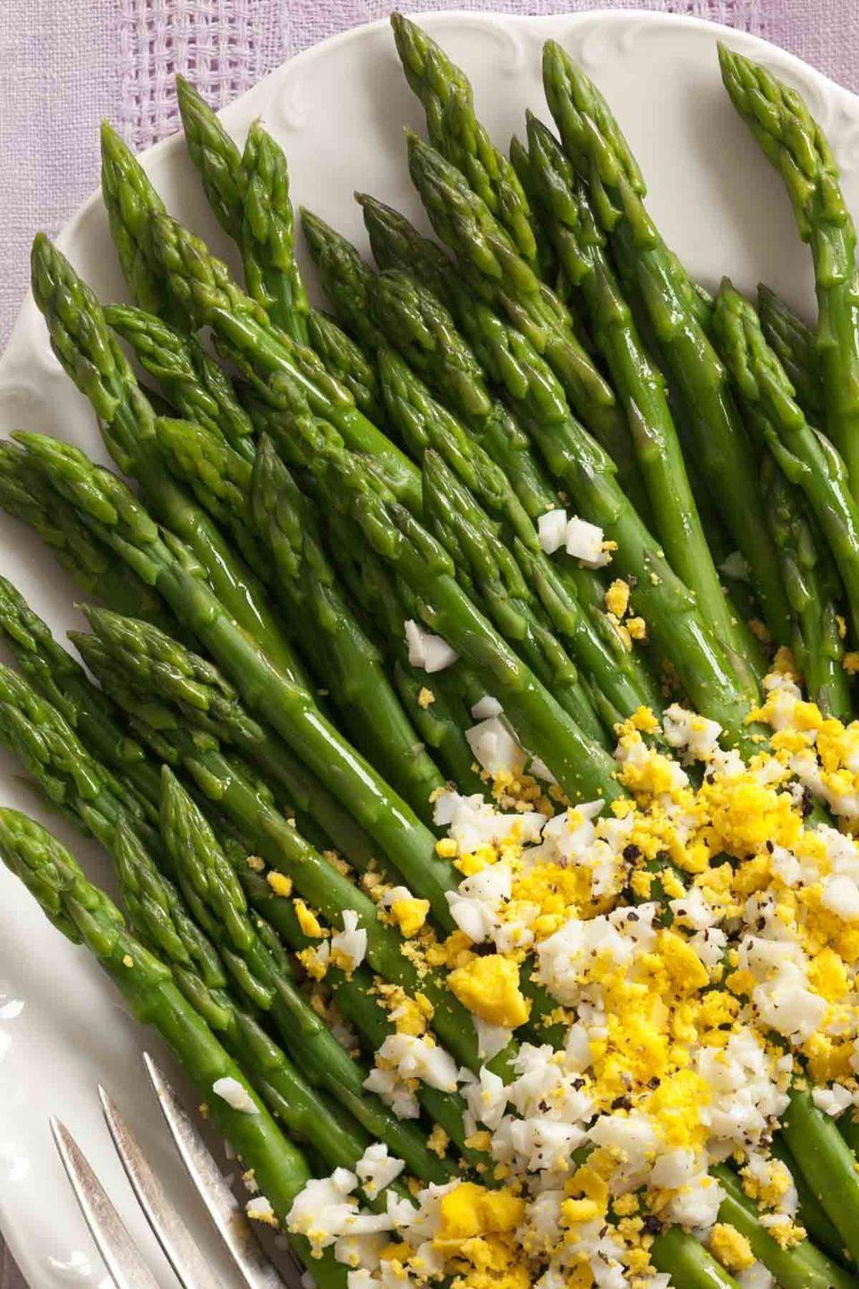"""<p>Looking for a quick side dish? These egg-covered asparagus are packed protein and flavor. </p><p><a href=""""https://www.womansday.com/food-recipes/food-drinks/recipes/a39001/asparagus-eggs-mimosa-recipe-ghk0413/"""" rel=""""nofollow noopener"""" target=""""_blank"""" data-ylk=""""slk:Get the Asparagus with Eggs Mimosa recipe."""" class=""""link rapid-noclick-resp""""><strong><em>Get the Asparagus with Eggs Mimosa recipe.</em></strong></a> </p>"""