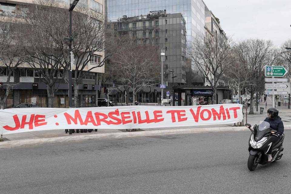 A man on a scooter looks over at a banner hung by Olympique de Marseille football club fans against the club's president Jacques-Henry Eyraud, that reads in French 'JHE: Marseille vomits you', a few hours before the Ligue 1 match against Rennes in the southern French city of Marseille on January 30, 2021.