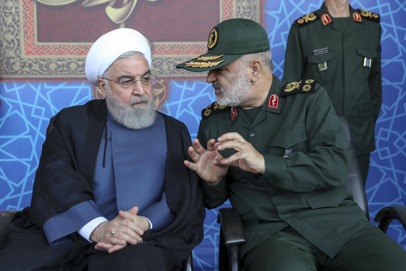 In this photo released by the official website of the office of the Iranian Presidency, President Hassan Rouhani, left, listens to chief of the Revolutionary Guard Gen. Hossein Salami at a military parade marking 39th anniversary of outset of Iran-Iraq war, in front of the shrine of the late revolutionary founder Ayatollah Khomeini, just outside Tehran, Iran, Sunday, Sept. 22, 2019. Rouhani said Sunday his country should lead regional security in the strategic Persian Gulf and warned against the presence of foreign forces, as the country's nuclear deal with world powers collapses and the U.S. deployed more troops to boost security for its Arab allies. (Iranian Presidency Office via AP)