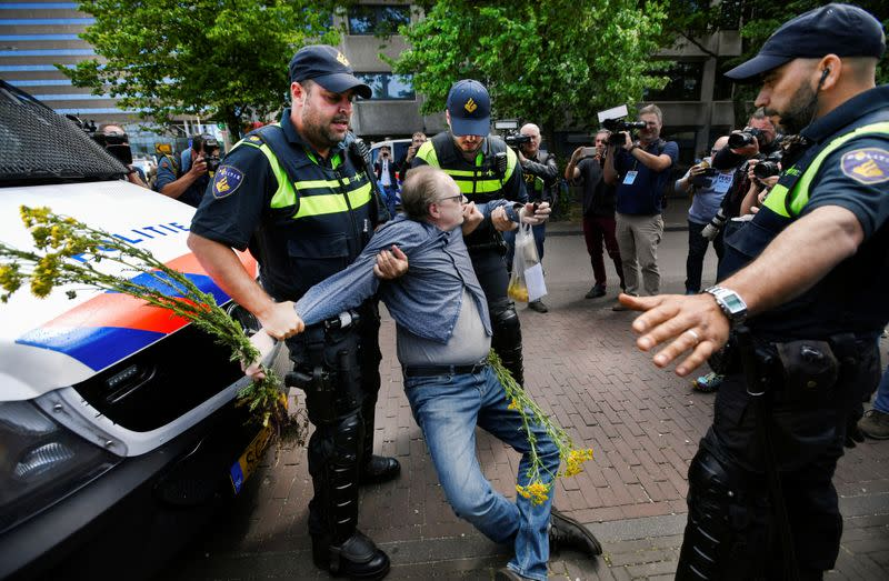 Police officers detain a demonstrator during a protest against the coronavirus disease (COVID-19) social distancing measures, in The Hague