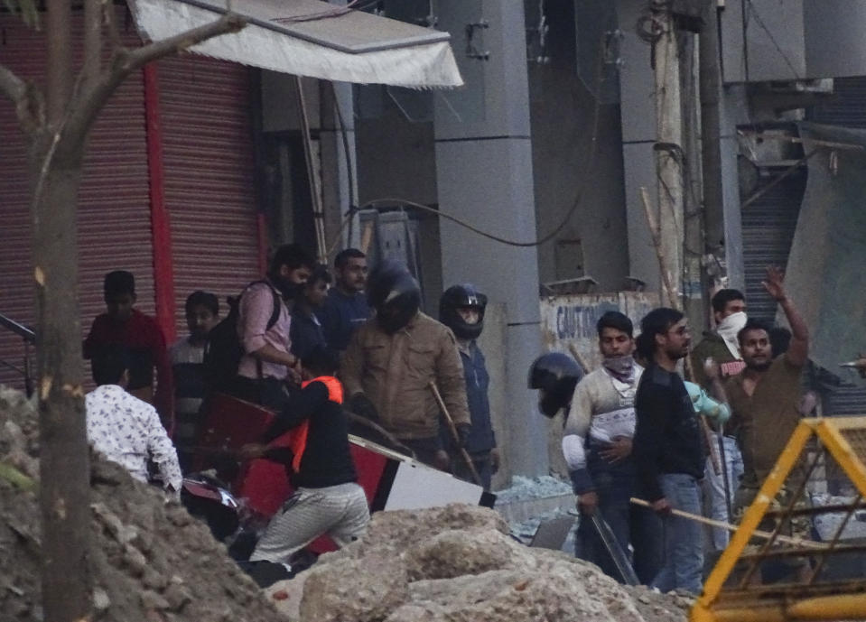 A mob vandalizes a shop during violence between two groups in New Delhi, India, Tuesday, Feb. 25, 2020. At least 23 people were killed in three days of clashes that cast a shadow over U.S. President Donald Trump's visit to the country. (AP Photo)