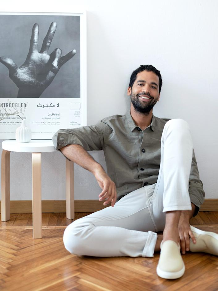"""<div class=""""caption""""> Alexandre-Camille Removille lounges in his Milan flat beside a white stool by <a href=""""https://www.artek.fi/en/products/stool-60"""" rel=""""nofollow noopener"""" target=""""_blank"""" data-ylk=""""slk:Alvar Aalto"""" class=""""link rapid-noclick-resp"""">Alvar Aalto</a>, an Irving Penn poster from a 2019 exhibition in Beirut, and a vase by <a href=""""https://www.richardginori1735.com/us/en-manifattura-1946"""" rel=""""nofollow noopener"""" target=""""_blank"""" data-ylk=""""slk:Richard Ginori from the Manifattura 1946 collection."""" class=""""link rapid-noclick-resp"""">Richard Ginori from the Manifattura 1946 collection.</a> </div>"""