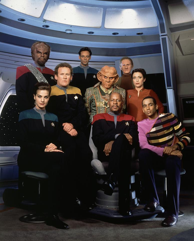 <p>Setting a series aboard a shared space station, as opposed to a Federation vessel, allowed <em>Deep Space Nine </em>to expand on the franchise's character and costume profile. The darker Starfleet jumpsuits reflect the show's own darker, more complex storytelling, and the prominent ppresenceof Bajoran and Ferengi fashions in the frame speaks to the mix of cultures that inhabit this deep space outpost.<br /><br />(Photo: CBS) </p>