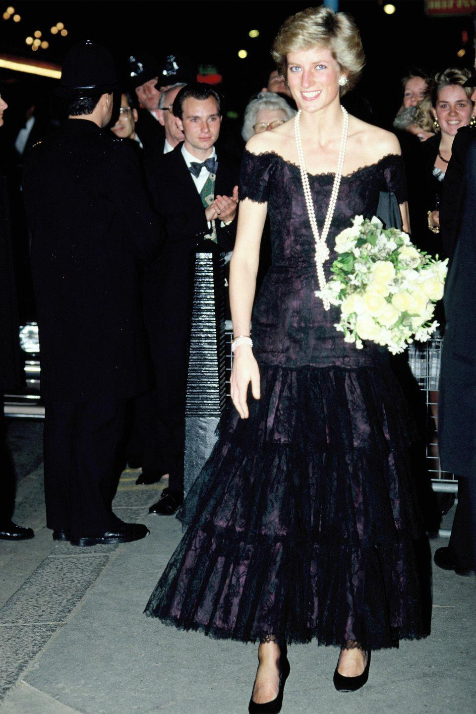 <p>In an off-the-shoulder black dress. </p>