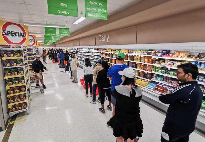 People queueing for a delivery of toilet paper, paper towel and pasta at Coles Supermarket, Epping