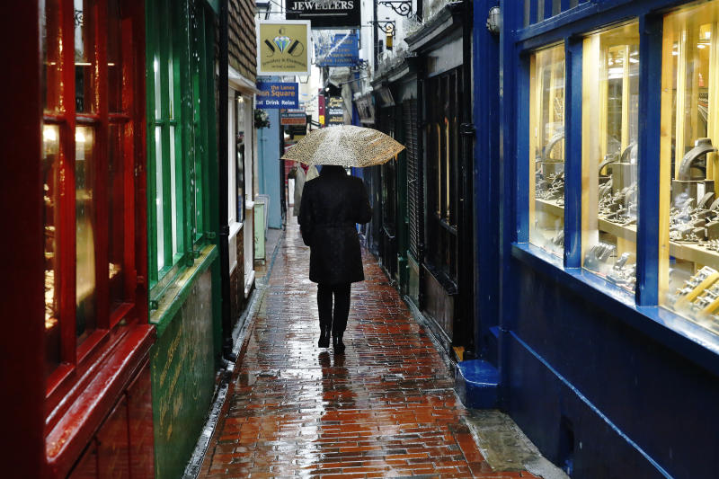 """A woman carrying an umbrella walks through """"The Lanes"""" shopping area in Brighton, southern England January 8, 2015. British businesses enjoyed a strong end to 2014, marked by rising demand at home and abroad and a record number of companies hiring staff, a major business survey showed on Thursday. REUTERS/Luke MacGregor (BRITAIN - Tags: BUSINESS ENVIRONMENT)"""