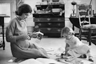 <p>Jackie scrapbooks newspaper clippings with her young daughter, Caroline, while her husband is on the presidential campaign trail.</p>