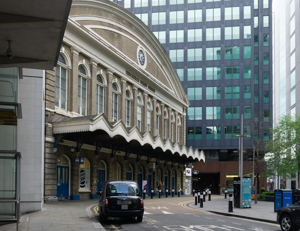 View of fron of Fenchurch street station on a weekend when it is shut as it serves weekday commuter traffic. The building dates back to 1850's. A black London taxi is stopped outside