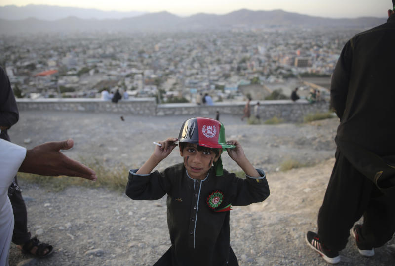 A boy poses with a hat which depicts the Afghan flag on Independence Day, in Kabul, Afghanistan, Monday, Aug. 19, 2019. Afghanistan's president is vowing to eliminate all safe havens of the Islamic State group as the country marks a subdued 100th Independence Day after a horrific wedding attack claimed by the local IS affiliate. (AP Photo/Rafiq Maqbool)