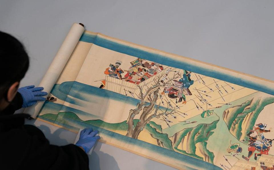 Collections digitisation assistant Ayesha Hussain unrolls one of three Japanese scrolls (Joe Giddens/PA) (PA Wire)