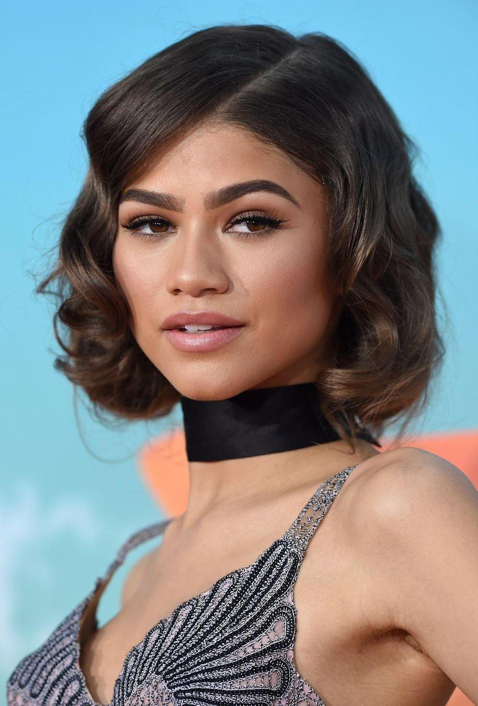 <p>The curly bob, slanted side part, and bold brows scream timeless glam.</p>