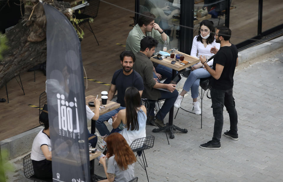 In this photo taken Saturday, June 6, 2020, people sit outside a cafe, in Ankara, Turkey. Images on social media and news agencies showed crowds picnicking and partying Saturday night without heeding to the rules of social distancing and wearing masks on the first weekend with no lockdown, prompting a reprimand from the health minister who warned that the novel coronavirus continued to pose a threat. (AP Photo/Burhan Ozbilici)