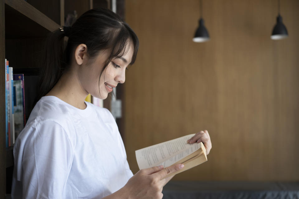 Young woman reading a book in a library.