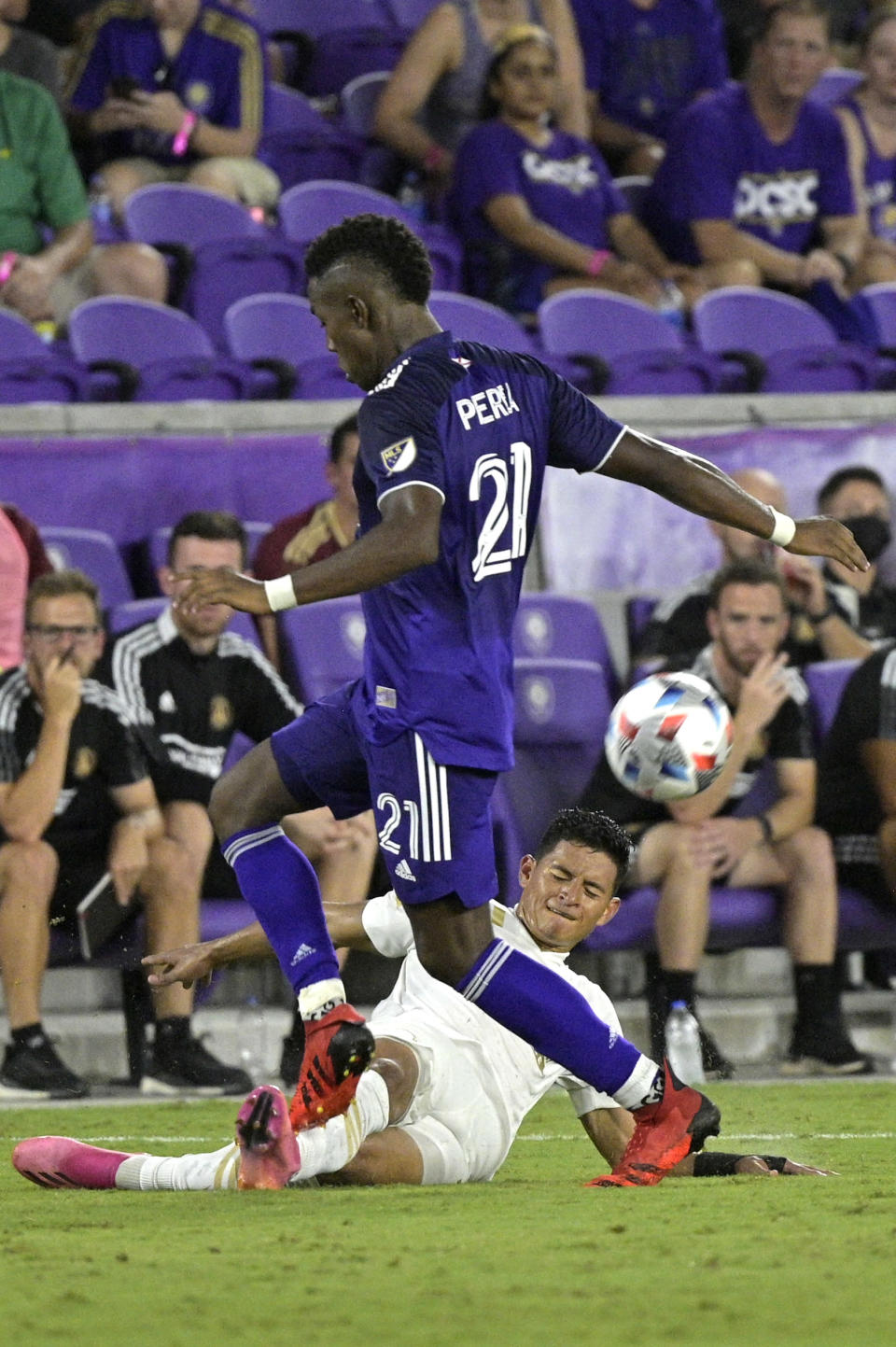 Orlando City midfielder Andres Perea (21) and Atlanta United defender Ronald Hernandez, below, compete for the ball during the second half of an MLS soccer match Friday, July 30, 2021, in Orlando, Fla. (Phelan M. Ebenhack/Orlando Sentinel via AP)