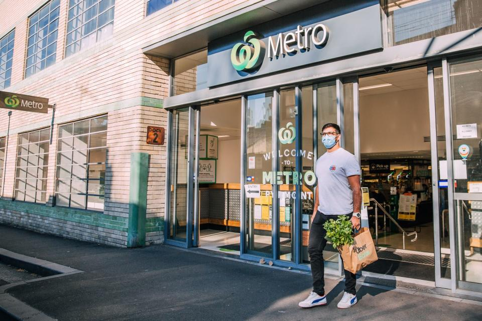 Uber Eats delivery man walking out of a Woolworths Metro store. Source: Woolworths