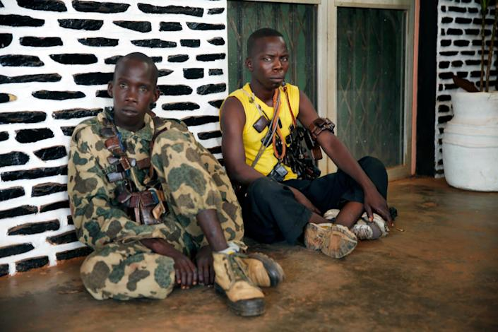 Seleka soldiers wearing lucky charms around their necks wait outside Bangui's hospital, Bangui, Central African Republic, Thursday, Dec. 5, 2013 following a day-long gun battle between Seleka soldiers and Christian militias. Fighting came to the capital of Central African Republic on Thursday, leaving dozens of casualties and posing the biggest threat yet to the new government just as the U.N. Security Council authorized an intervention force to prevent a bloodbath between Christians and Muslims. (AP Photo/Jerome Delay)