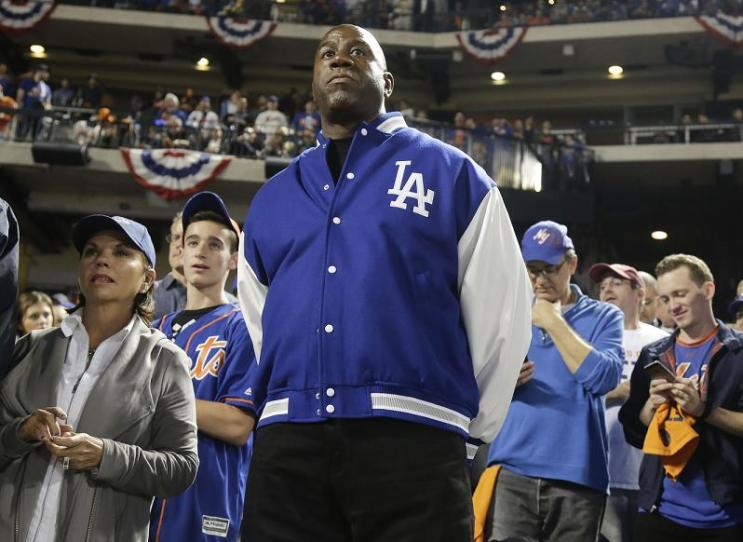 Dodgers co-owner Magic Johnson, seen here in 2015, is balancing his time between the Dodgers and Lakers. (AP)
