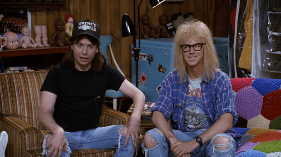 <p><strong>For Wayne:</strong> Black Converse sneakers, old ripped jeans, a long brown wig, a black t-shirt, and a black <strong>Wayne's World</strong> hat.</p> <p><strong>For Garth:</strong> Black Converse sneakers, washed-out jeans, a white band t-shirt under a blue plaid shirt with rolled-up sleeves, a shaggy blond wig, and black-rimmed glasses.</p>