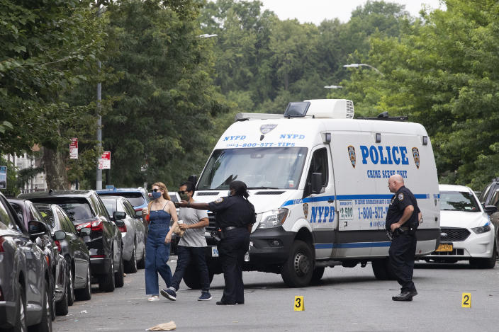Police direct pedestrians away from the crime scene of a shooting in the Crown Heights neighborhood which left one dead and five injured, Wednesday, July 15, 2020, in the Brooklyn borough of New York. (AP Photo/Mark Lennihan)