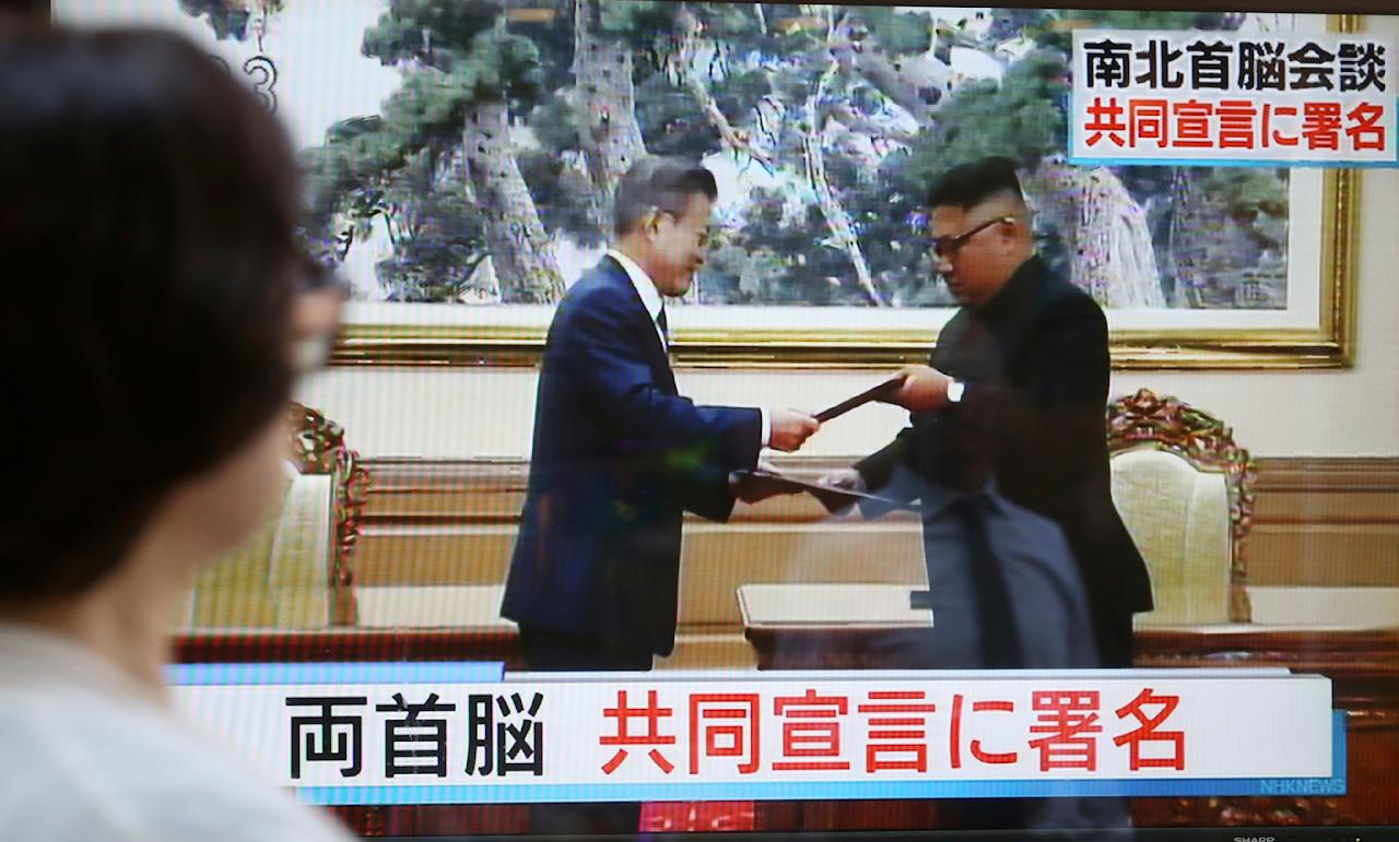 """A woman watches a TV screen showing North Korean leader Kim Jong Un, right, and South Korean President Moon Jae-in exchange signed documents in Pyongyang, North Korea, on a news program in Tokyo, Wednesday, Sept. 19, 2018. Japanese characters at bottom read: """"Both leaders signed a joint declaration."""" (AP Photo/Koji Sasahara)"""