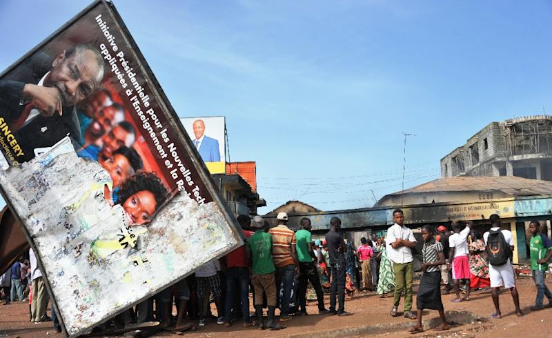 People gather around a destroyed commercial building on October 10, 2015 in Conakry, after clashes between rival political parties ahead of Guinea's presidential election on October 11, 2015