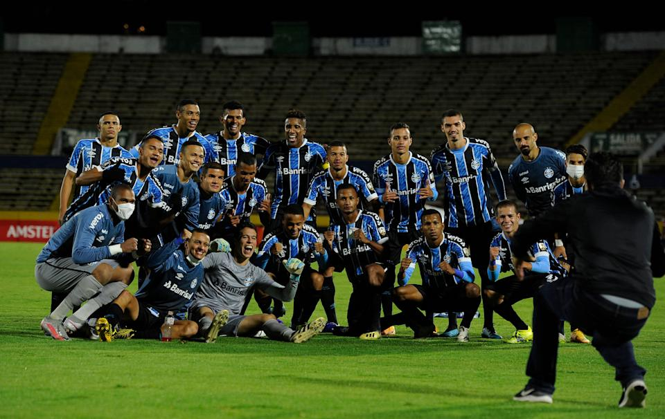 Brazil's Gremio football players pose for pictures as they celebrate after winning the Copa Libertadores football tournament second round match between against Ecuador's Ayacucho at the Atahualpa Olympic Stadium in Quito on March 16, 2021. (Photo by SANTIAGO ARCOS / POOL / AFP) (Photo by SANTIAGO ARCOS/POOL/AFP via Getty Images)