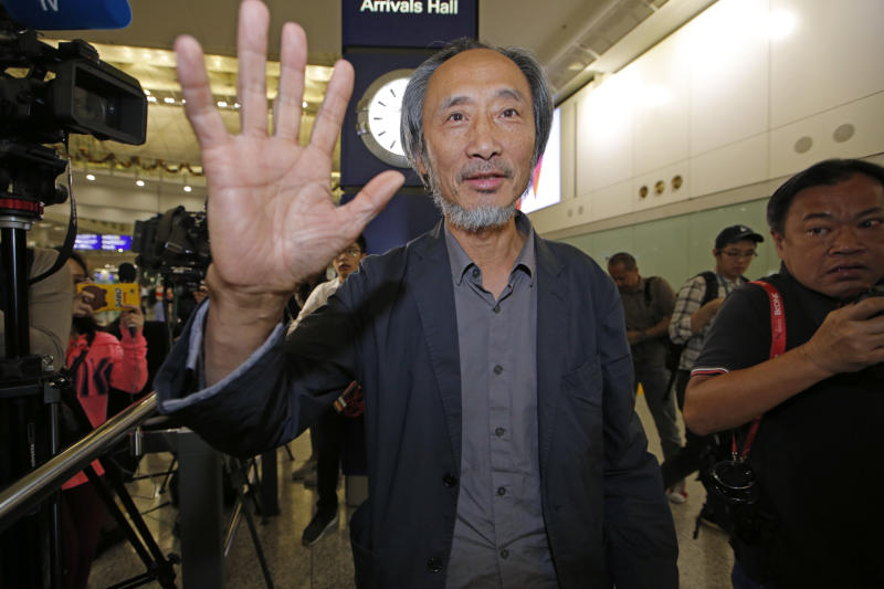"""Chinese dissident writer Ma Jian waves to media after arriving Hong Kong international airport, Friday, Nov. 9, 2018. Despite Mallet's rejection, Hong Kong on Friday permitted dissident writer Ma Jian to enter to attend a literary festival, even after an arts venue in the city canceled his appearance. Ma, whose novels frequently satirize China's communist leaders, told reporters he experienced nothing unusual while passing through passport control and that organizers were still lining-up a place for him to speak. """"The lecture will definitely happen. If there is a single Hong Kong person who is willing to listen, or a single reader who contacts me, I will be there,"""" Ma said. (AP Photo/Kin Cheung)"""