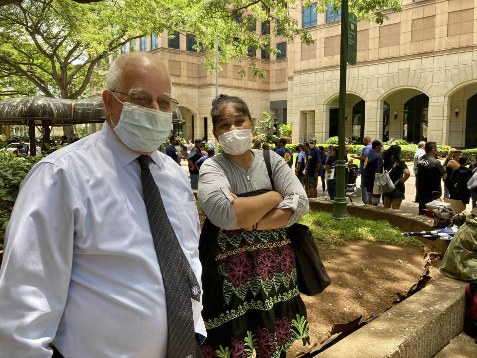 Attorney Eric Seitz and his client Yovita Sykap wait to enter a courthouse on Tuesday, July 20, 2021, in Honolulu where a judge is scheduled to consider whether there's probable cause to support murder and attempted murder against three police officers in the shooting that killed Sykap's 16-year-old son. (AP Photo/Jennifer Sinco Kelleher)