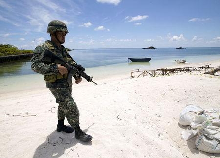 FILE PHOTO: A Filipino soldier patrols at the shore of Pagasa island (Thitu Island) in the Spratly group of islands in the South China Sea, west of Palawan, Philippines