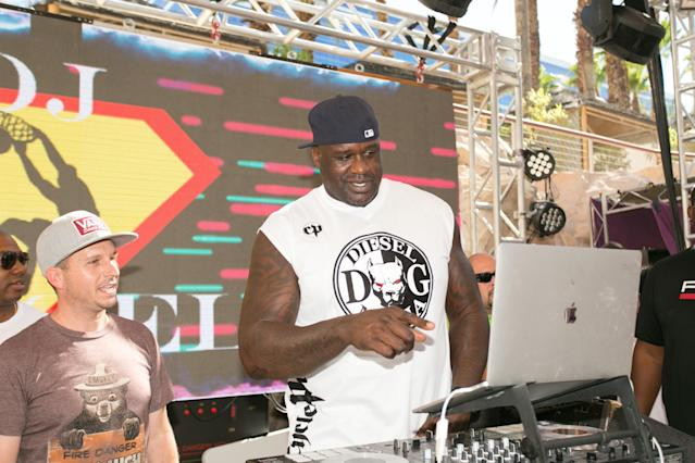 Shaquille O'Neal checks the Kings' transactions list between songs in his DJ set at Rehab Beach Club in Las Vegas. (AP)