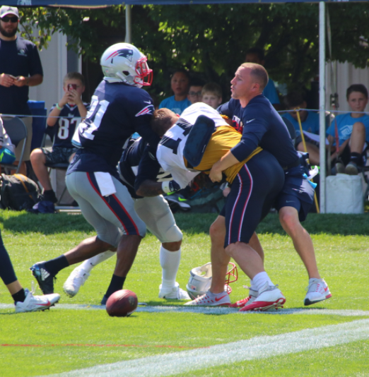 Patriots CB Stephon Gilmore, left, and Julian Edelman, center, fight at practice on Tuesday while a team staff member tries to separate them. (Shaun Ganley/Instagram)