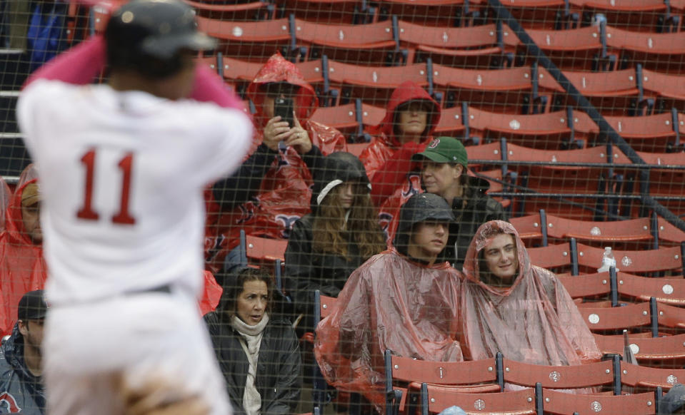Boston Red Sox's Rafael Devers (11) takes his at-bat as fans watch in the rain in the seventh inning of a baseball game against the Seattle Mariners at Fenway Park, Sunday, May 12, 2019, in Boston. (AP Photo/Steven Senne)