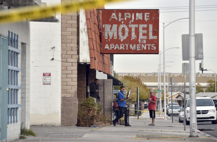Investigators work at the scene of a fire at a three-story apartment complex early Saturday, Dec. 21, 2019 in Las Vegas. The fire was in first-floor unit of the Alpine Motel Apartments and its cause was under investigation, the department said. Authorities say multiple fatalities were reported and many more were injured. (AP Photo/David Becker)