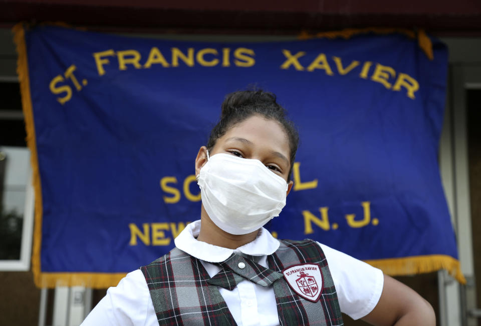 """Miranda Gonzalez, 9, a former third grade student at St. Francis Xavier School, poses for a portrait in front of the building Thursday, Aug. 6, 2020, in Newark. The Archdiocese of Newark announced the school's closure just four weeks before the new academic year. """"I'm very disappointed and very sad,"""" said Miranda's mother, Wanda Gonzalez. """"The area needs a Catholic school."""" (AP Photo/Jessie Wardarski)"""