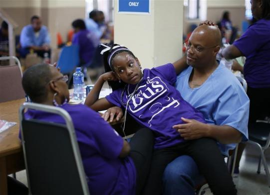 Troyanna (C), 10, sits on the knee of her father Troy, 49, as he talks to her mother Zunknie, 38, after meeting him for the first time at San Quentin state prison in San Quentin, California June 8, 2012.