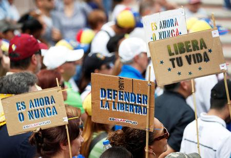 "Supporters of Venezuela's opposition leader Juan Guaido attend a rally with members of the Venezuela's National Assembly regarding an amnesty law project for members of the military, in Caracas, Venezuela, January 26, 2019. Placards read: ""it's now or never"", ""defending freedom"", ""free your life"". REUTERS/Carlos Garcia Rawlins"